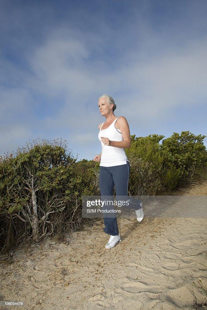 Senior jogging down a dirt road : Stock Photo