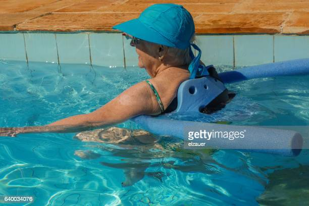 A Senior lady exercising with a noodle float in a swimming pool.