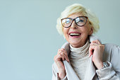 beautiful senior lady in trench coat and eyeglasses, isolated on grey