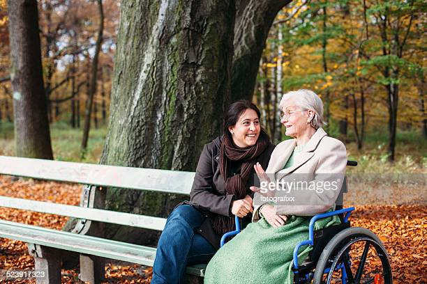 Senior lady in wheelchair together with young woman