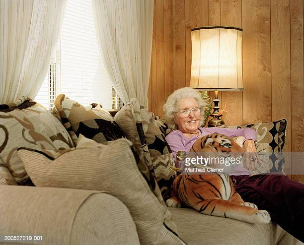 Senior lady sitting on couch with stuffed animal