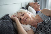 Portrait of senior lady sleeping in comfortable bed with husband