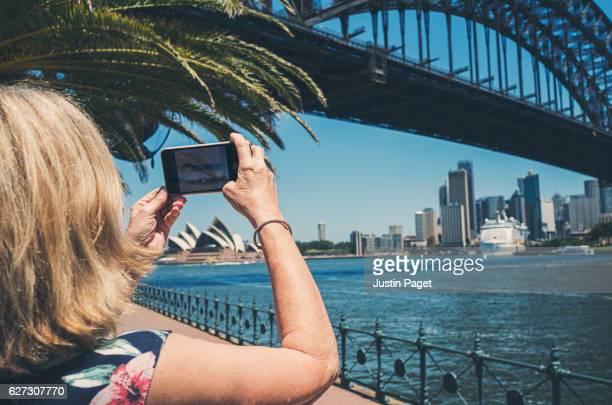 Senior Lady taking photo of Sydney Harbour Bridge