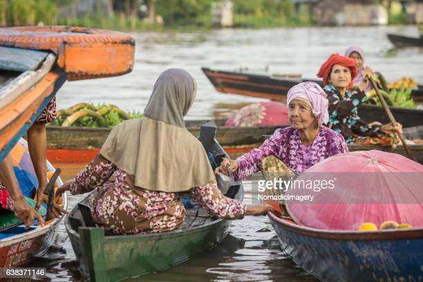 Senior lady trades from a boat at the floating market