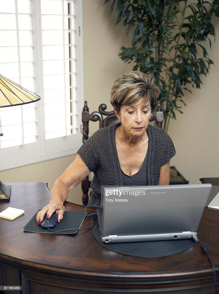 Senior lady using computebrowsing internet  : Stock Photo