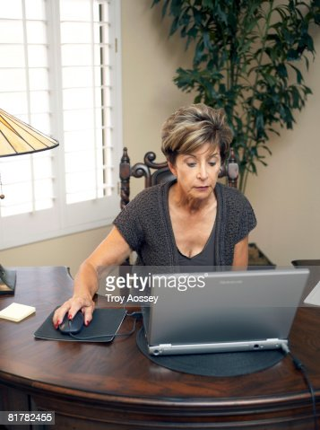 Senior lady using computebrowsing internet  : Stock Photo