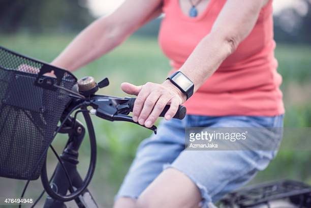 Senior lady using smart watch while cycling.