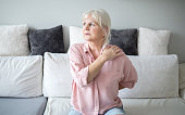 Portrait of senior lady with back pain sitting on couch