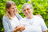 Picture of a happy senior lady wearing glasses with her beautiful granddaughter in the garden
