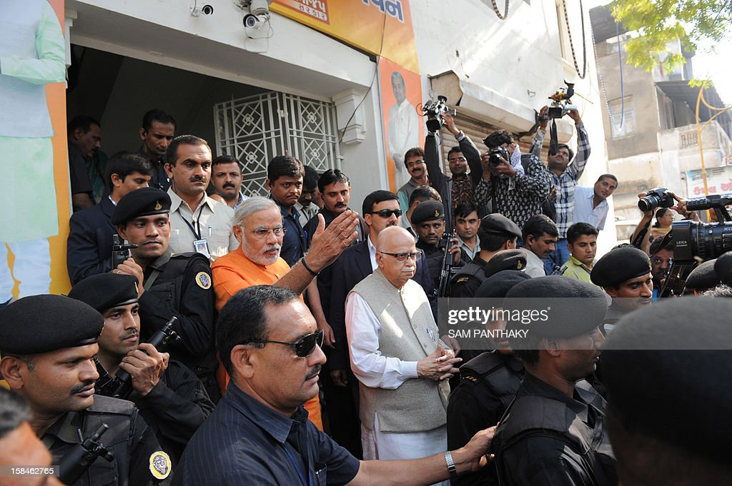 Senior leader of Bharatiya Janta Party (BJP) Lal Krishna Advani (centre R, in grey) and Western India's Gujarat state Chief Minister, Narendra Modi (centre L) exit the Gujarat BJP headquarters in Ahmedabad on December 17, 2012. Millions of Indians are voting in the final stage of Gujarat state elections with Hindu nationalist Narendra Modi seeking a clear victory to bolster his prime ministerial ambitions in 2014. AFP PHOTO/Sam PANTHAKY
