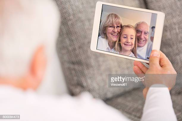 Senior looking at digital tablet with family portrait