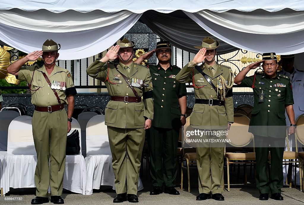Senior Malaysian and Australian Military officials pay their last respects during a repatriation ceremony at the Royal Malaysian Airforce base in Subang on May 31, 2016. Decades after the end of the Vietnam war and the brutal fight against communists insurgency in Malaysia, the remains of 24 Australians soldiers and eight dependents were returned home. / AFP / MANAN