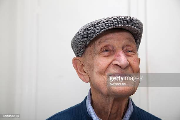 Senior male 90 years old wearing grey herringbone flat cap