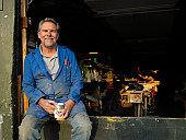 Senior male boat builder in workshop holding mug, smiling, portriat