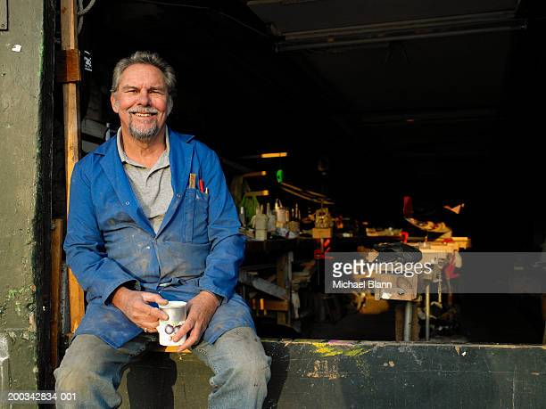Senior male boat builder in workshop holding mug, smiling, portriat
