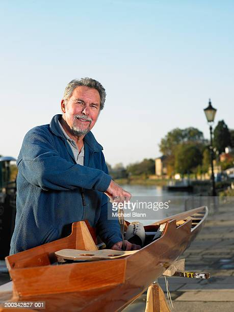 Senior male boat builder working on boat outdoors, smiling, portriat