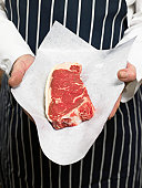 Senior male butcher holding sirloin of steak, mid section