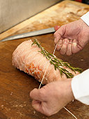 Senior male butcher tying rosemary to joint of meat, close-up of hands
