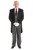 Senior male butler, hands clasped, portrait