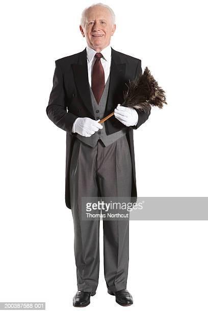 Senior male butler holding feather duster, smiling, portrait