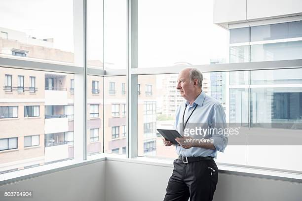 Senior male consultant with tablet by hospital window