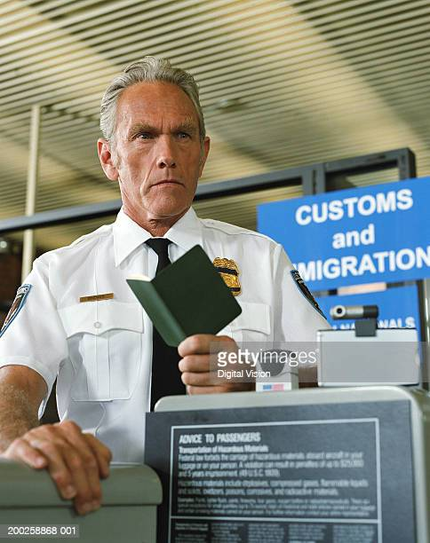 Senior male customs officer holding passport, frowning