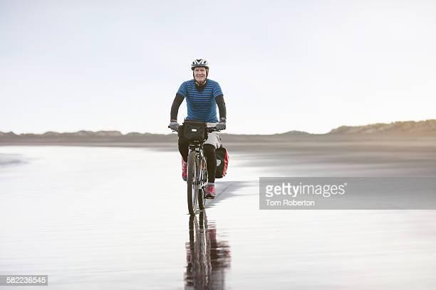 Senior male cycling on desolate beach