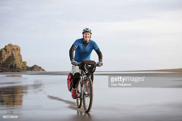 Senior male cycling on desolate beach