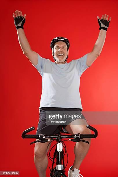 Senior male cyclist celebrating