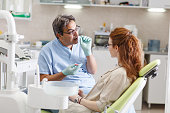 Senior male dentist in dental office talking with female patient and preparing for treatment.