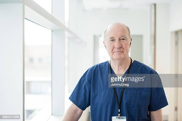 Senior male doctor in blue uniform looking at camera