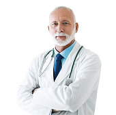 Closeup front view of a senior male doctor standing in front of a camera with his arms folded. Shot over white background.