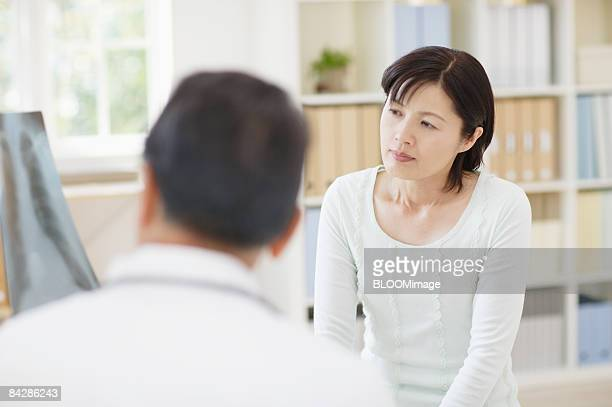 Senior male doctor talking to patient, focus on background