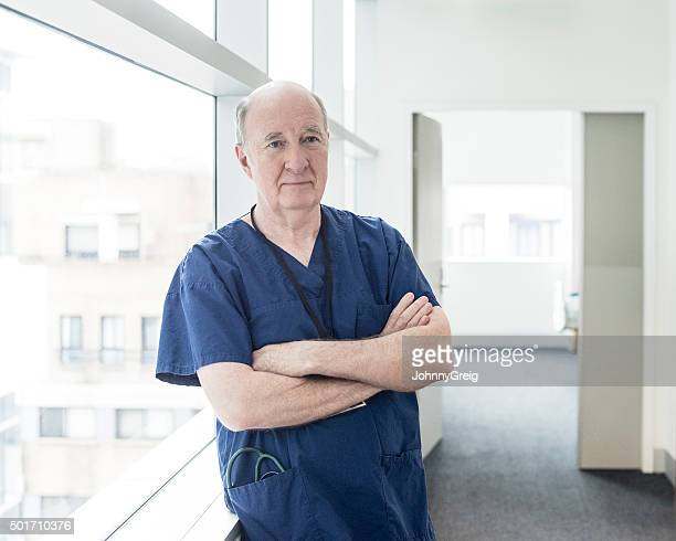 Senior male doctor with arms folded in hospital, portrait