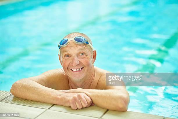 senior male enjoying a swim in vintage pool