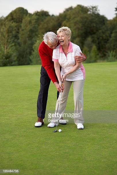 Senior male golfer teaching partner to putt.