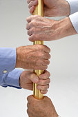 Senior male hands holding on to a golden bar