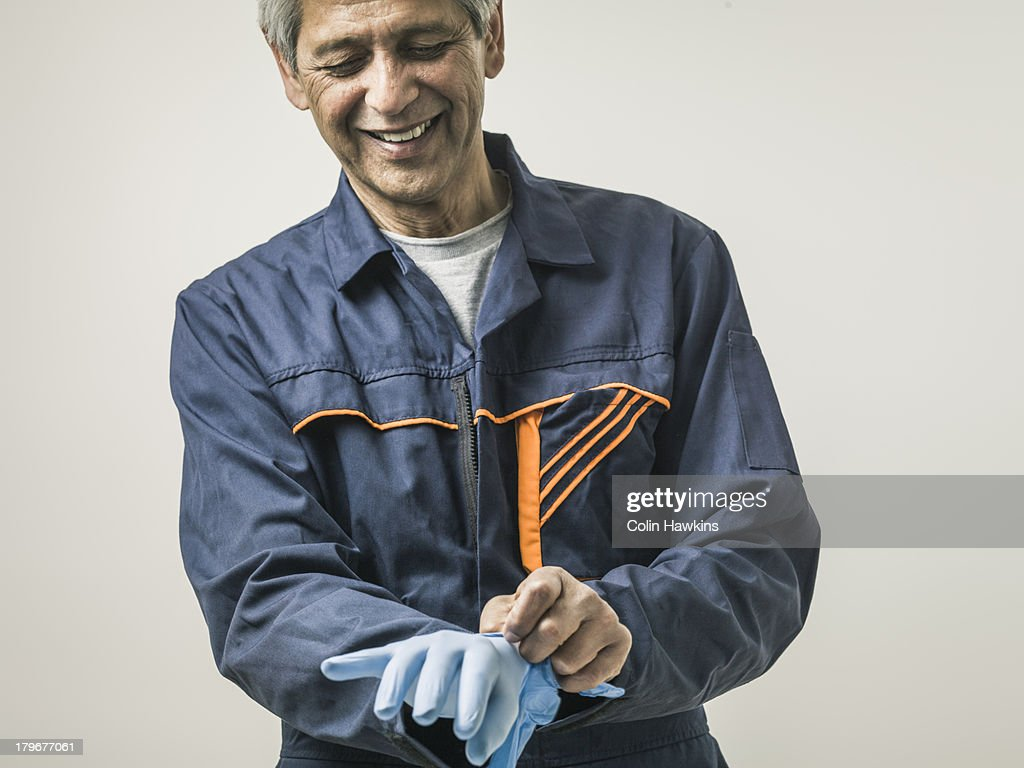 Senior male in overalls with protective gloveslov
