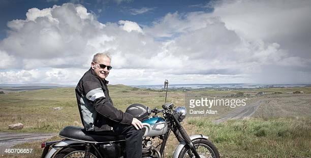 Senior male motorcyclist taking a break