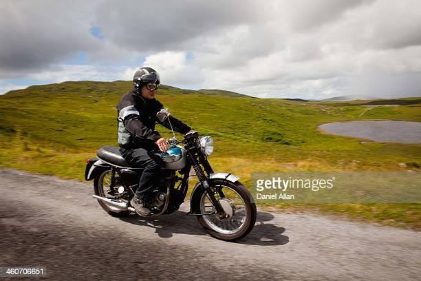 Senior male on motorbike on rural road