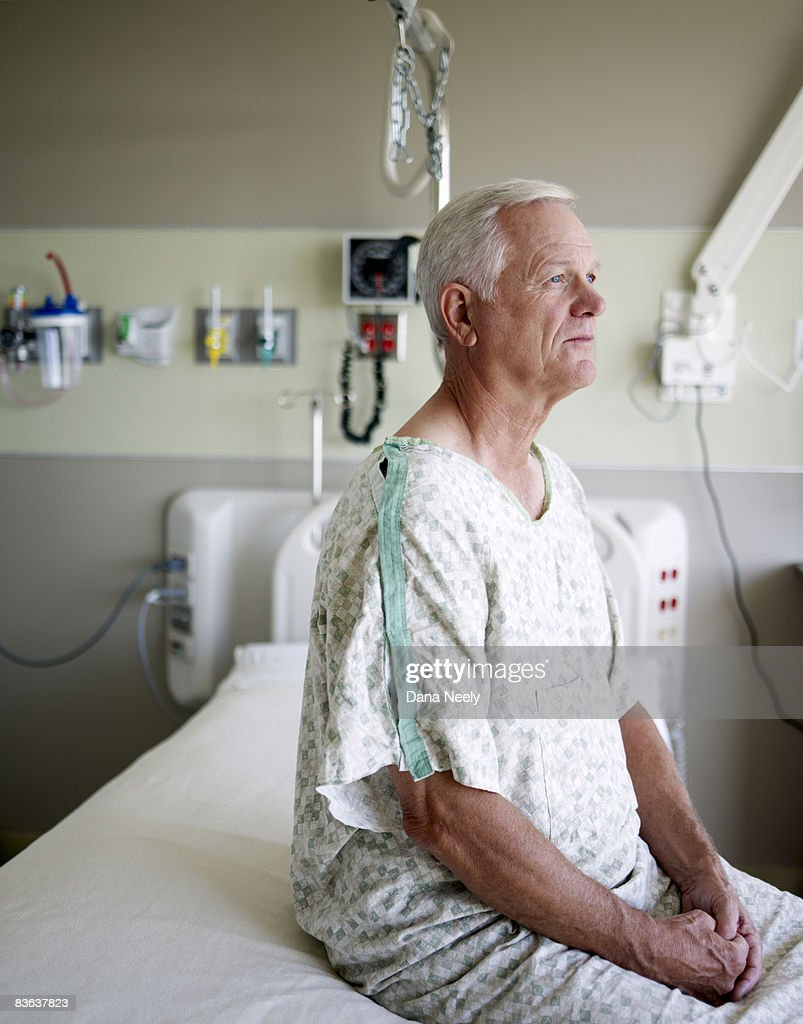 Senior male patient sitting on bed in hospital : Stock Photo