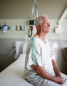 Senior male patient sitting on bed in hospital