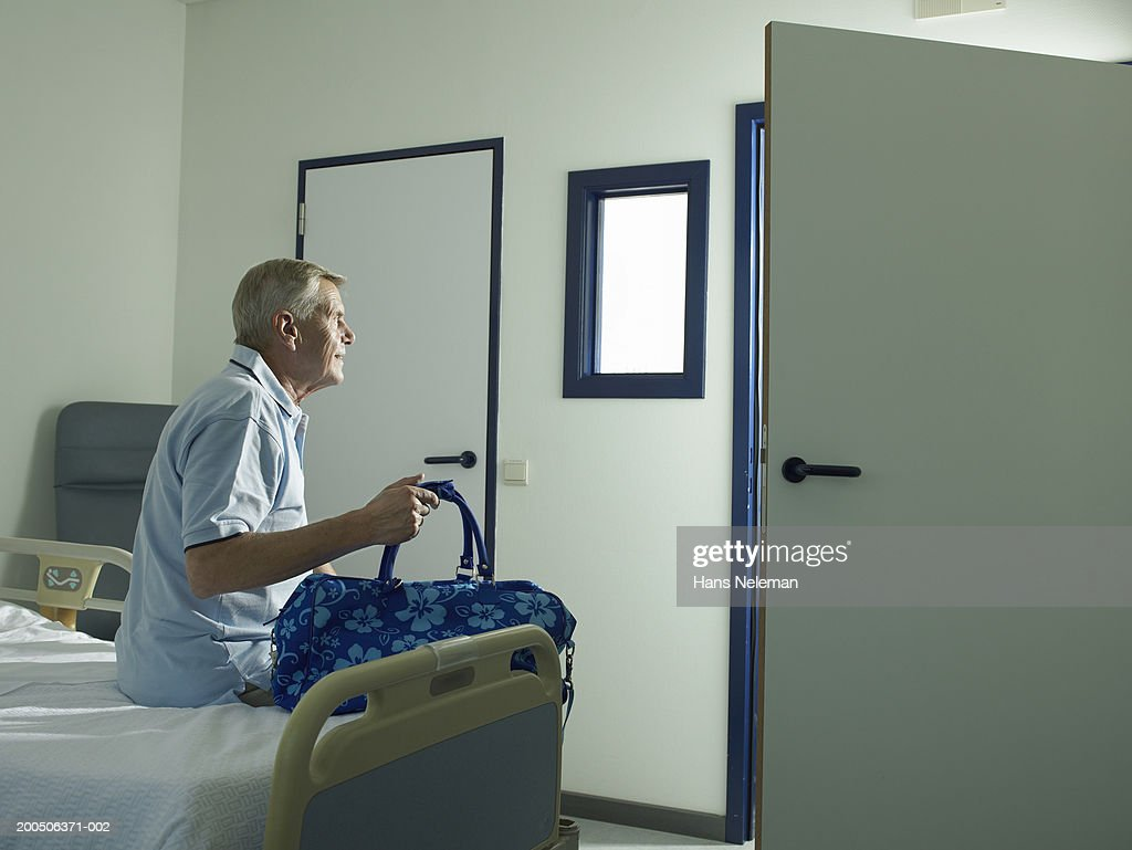 Senior male patient sitting on hospital bed, rear view