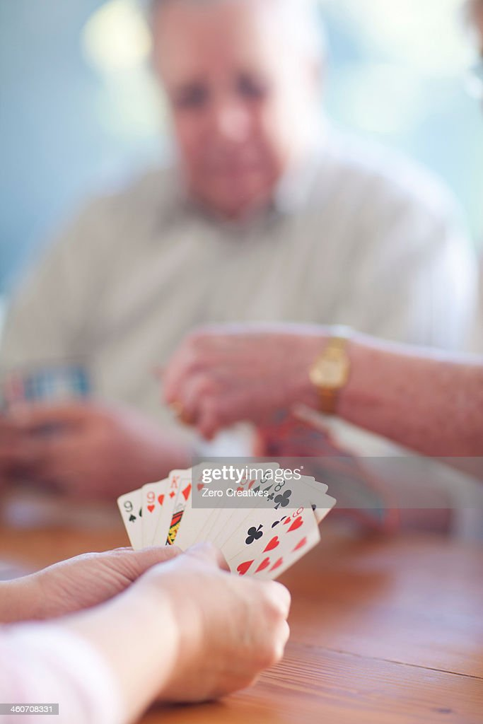 Senior male playing cards with family