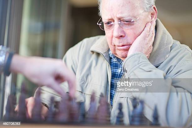 Senior male playing chess with son