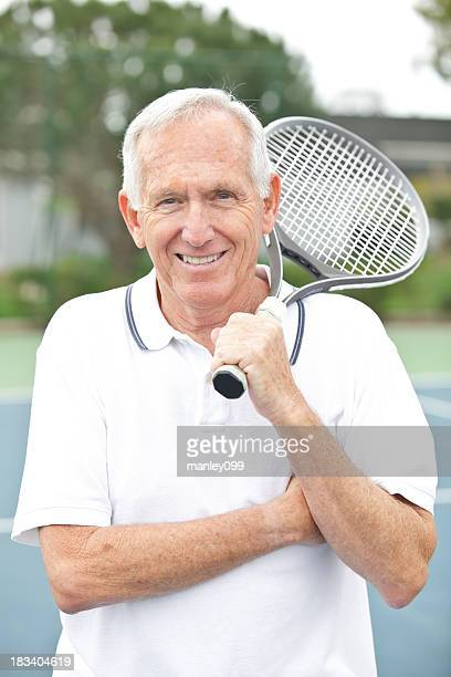 Senior male posing with a tennis racket and arms crossed