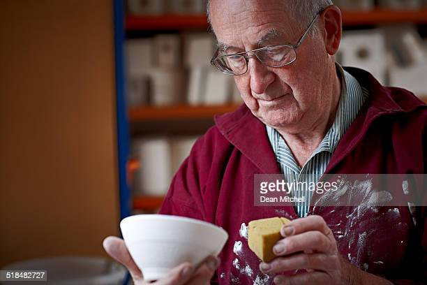 Senior male potter giving finishing touch to a clay pot