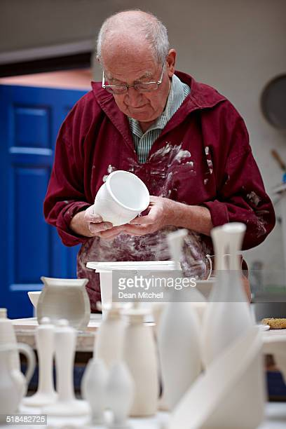 Senior male potter painting a clay pot