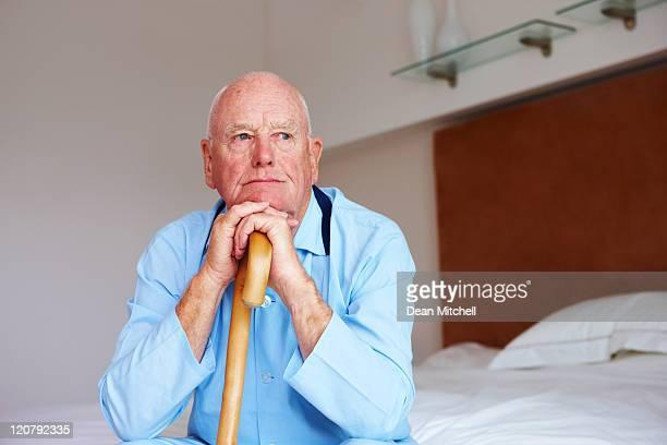 Senior homme au repos de menton sur les mains et Canne