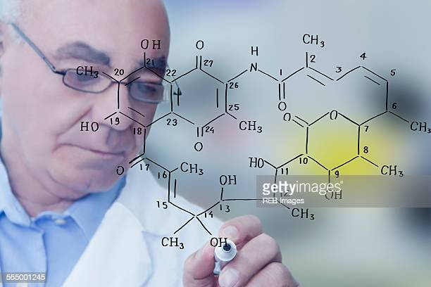 Senior male scientist writing molecular formula on clear board